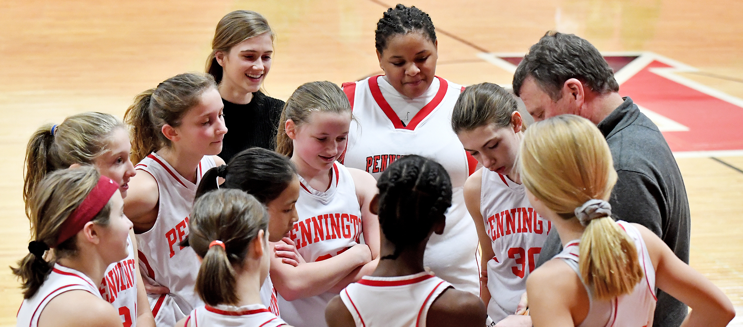 Girls' basketball team meets with the coach before a game